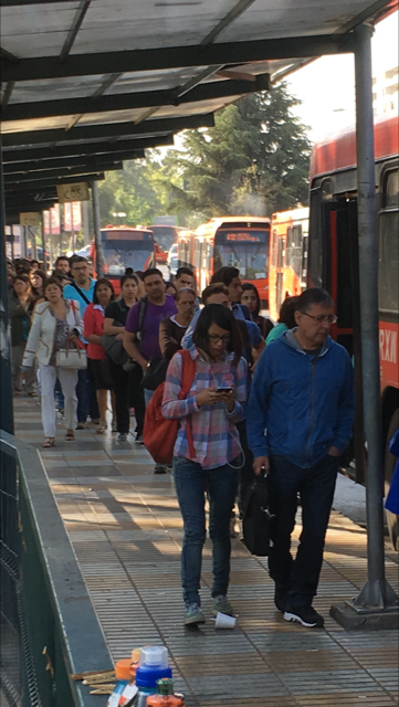 Long lines of passengers waiting for buses at Trans Santiago bus stop